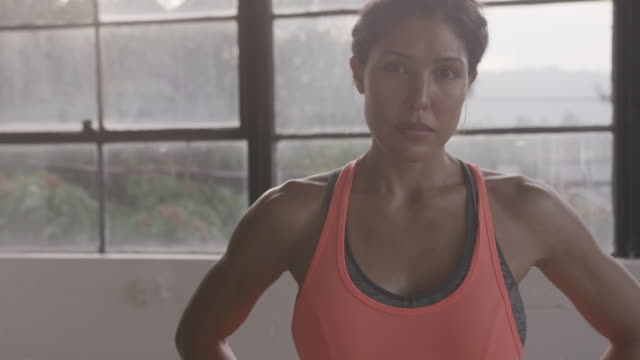 stockvideo's en b-roll-footage met handheld portrait of confident athlete with hands on hip standing against window at gym - one mid adult woman only