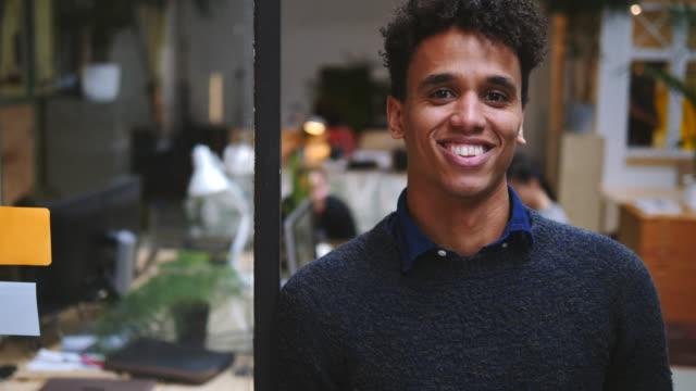 vídeos y material grabado en eventos de stock de handheld portrait of confident smiling businessman in office - cotrabajo