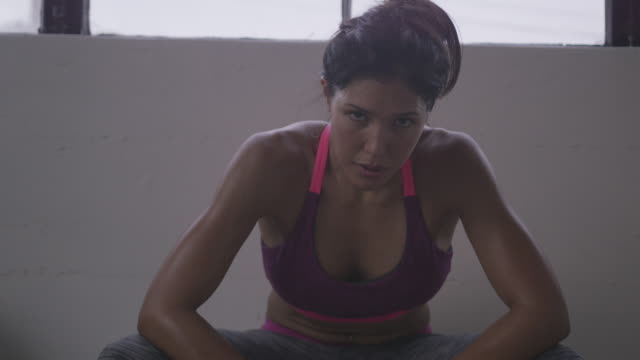 handheld portrait of exhausted female athlete sitting by wall in gym - staring stock videos & royalty-free footage