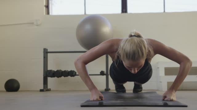 vídeos y material grabado en eventos de stock de handheld portrait of female athlete doing push-ups on exercise mat at gym - entrenamiento sin material