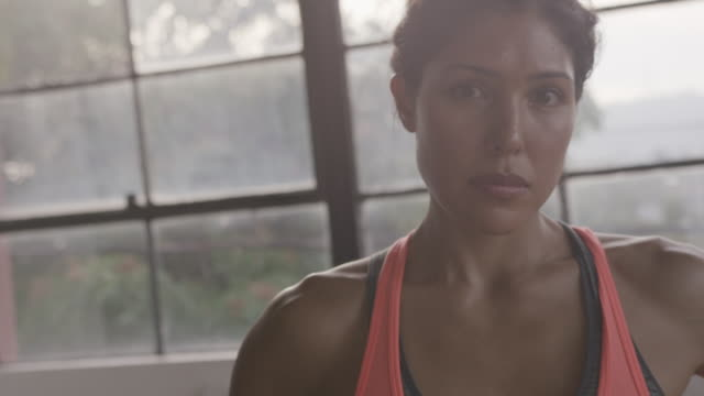stockvideo's en b-roll-footage met handheld portrait of female athlete with hands on hip standing against window at gym - one mid adult woman only