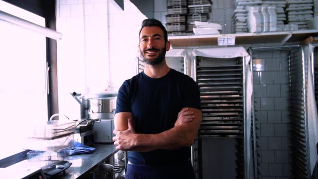 handheld portrait of happy chef standing in commercial kitchen - dreiviertelansicht stock-videos und b-roll-filmmaterial