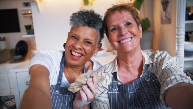 handheld portrait of happy women taking selfie through phone in workshop - mature women stock-videos und b-roll-filmmaterial
