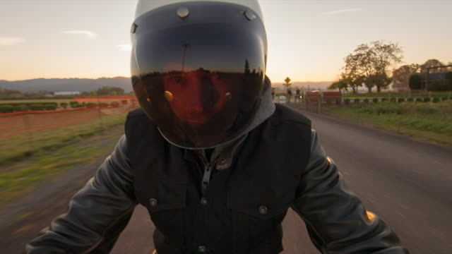Handheld portrait of man riding motorcycle on road against sky during sunset