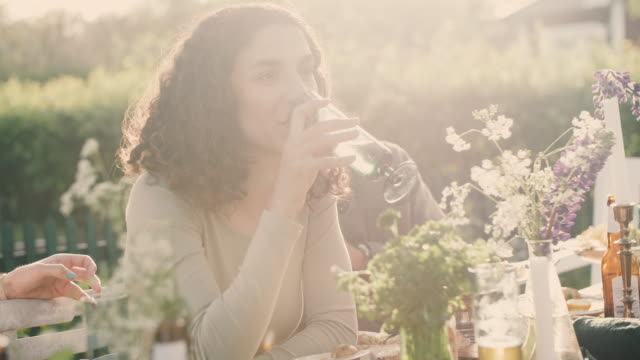 Handheld portrait of smiling woman drinking while sitting in yard during social gathering