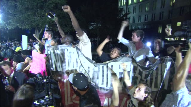 handheld ms of protesters outside at night - crime or recreational drug or prison or legal trial stock-videos und b-roll-filmmaterial