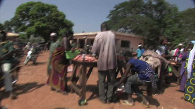 pov hand-held push-in - vendors prepare and sell raw, fresh meat at an open air market in benin. / benin - benin stock videos and b-roll footage