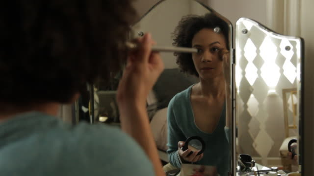 Handheld rear view of woman applying make-up at home