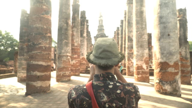 handheld rear view: Young traveler is taking the photo of Ruins in Sukhothai