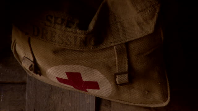 Handheld sequence showing a first aid kit satchel reading 'SHELL DRESSINGS' hanging inside a WWI trench dugout in northern France.