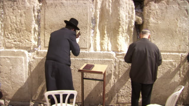 Handheld sequence showing Jewish worshippers praying at the Western Wall, Jerusalem.