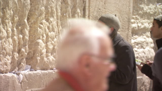 handheld sequence showing men praying at the western wall, jerusalem. - historical palestine stock videos & royalty-free footage