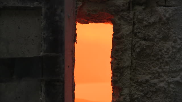 handheld sequence showing the crack of a partially open door of a fiercely-burning furnace, uk. - industrie ofen stock-videos und b-roll-filmmaterial