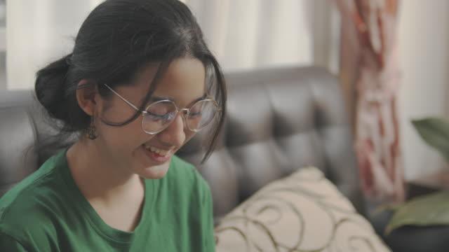 vidéos et rushes de handheld pov shot : adolescente asiatique lisant un livre analogique tout en restant à la maison. elle tourne page de livre d'apprentissage . étudiante asiatique étudiant les devoirs de leçon d'histoire de son école à sa maison. - doigt humain