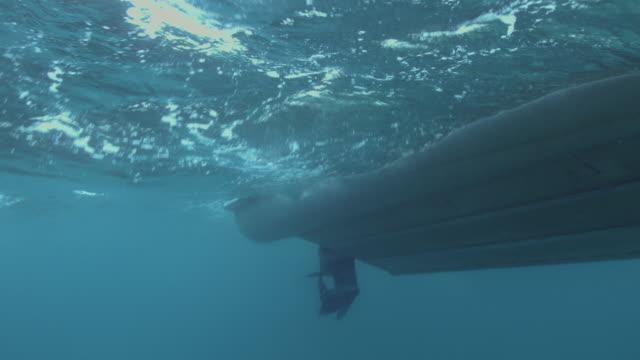 a handheld shot below surface of water towards boat - 船体点の映像素材/bロール