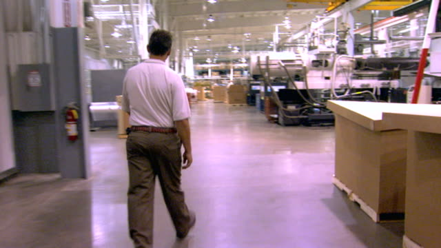 handheld shot, camera following a man walking through a factory - 2008 stock videos and b-roll footage
