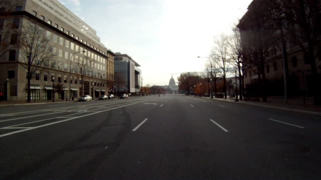 a handheld shot driving towards the u.s. capitol building in washington dc on a cloudy day. - bundesgebäude stock-videos und b-roll-filmmaterial
