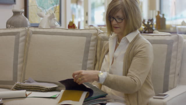 handheld shot female owner examining fabric swatch at furniture store - stoffmuster stock-videos und b-roll-filmmaterial