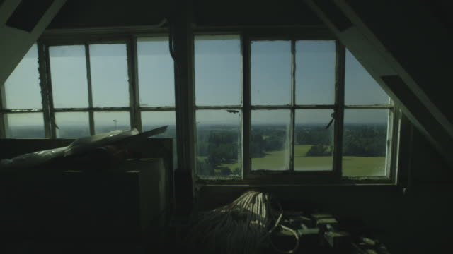 Handheld shot looking out at green fields through a high attic window, UK.