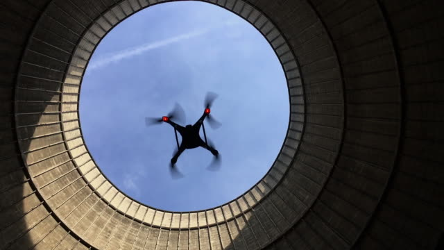 stockvideo's en b-roll-footage met handheld shot looking up at a quadcopter hovering in an abandoned cooling tower, charleroi, belgium - onbemand luchtvaartuig