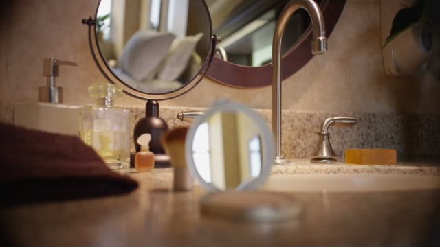 Handheld shot of a contemporary bathroom counter with sink, faucet, mirror and compact.