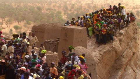 handheld shot of a crowd of people standing on a rock - tradition bildbanksvideor och videomaterial från bakom kulisserna