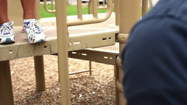 stockvideo's en b-roll-footage met handheld shot of a father with his kids at a playground. - familie met drie kinderen