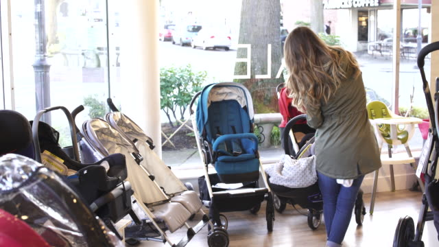 hand-held shot of a mother looking at strollers - pushchair stock videos and b-roll footage