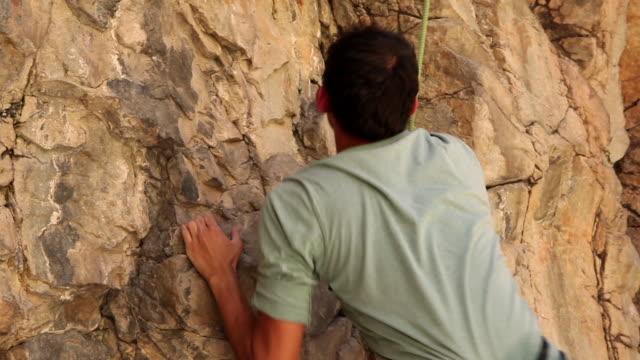 vidéos et rushes de handheld shot of a rock climber making his way up a cliff. - harnais de sécurité