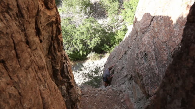 handheld shot of a rock-climber's hesitation. - rock face stock videos & royalty-free footage