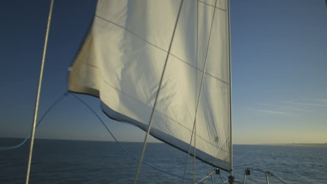 Handheld shot of a sail as it is furled on a moving yacht off the south coast of England, UK.
