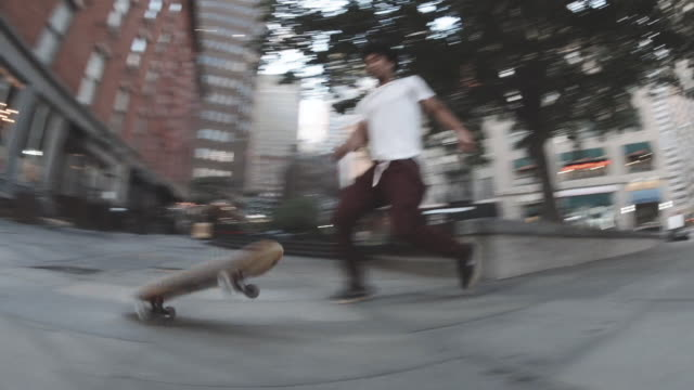 A handheld shot of a skateboarder falling off of a curb in Downtown Manhattan