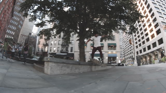 a handheld shot of a skateboarder falling off of a curb in downtown manhattan - 柵点の映像素材/bロール