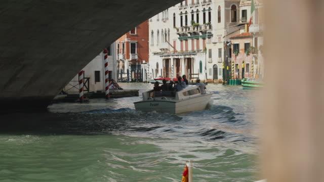 vídeos y material grabado en eventos de stock de handheld shot of a water taxi heading under a bridge on grand canal, venice, italy - embarcación de pasajeros