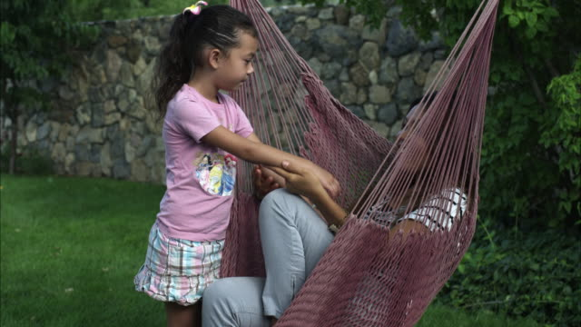 handheld shot of a young woman sitting in a hammock talking to a little girl - pantaloni video stock e b–roll