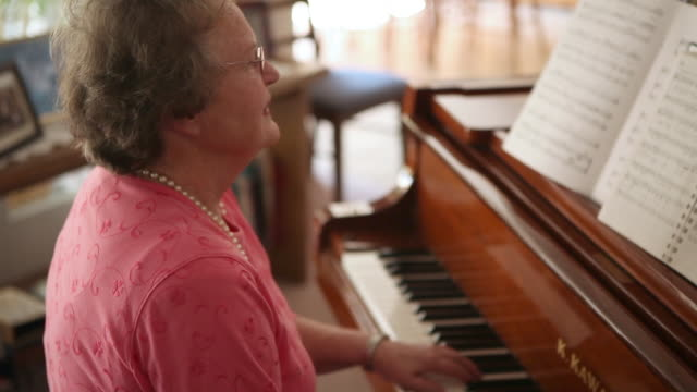 a handheld shot of an elderly woman playing the piano. - ピアノ点の映像素材/bロール