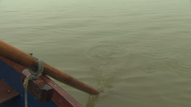 vidéos et rushes de handheld shot of an oar dipping into murky water of the river medway, kent, uk. - bateau à rames