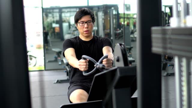 vídeos y material grabado en eventos de stock de tiro mano de hombre asiático de realizar nuevamente ejercicios: sentado bajo cable filas - press de banca