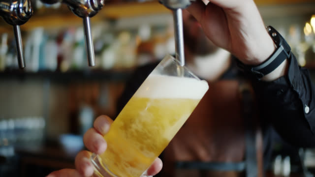 handheld shot of bartender pouring half pint of lager - pint glass stock videos & royalty-free footage