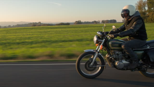 Handheld shot of biker gesturing while riding motorcycle on road during sunset