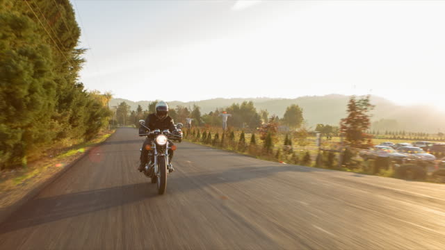 Handheld shot of biker riding motorcycle on road during sunset