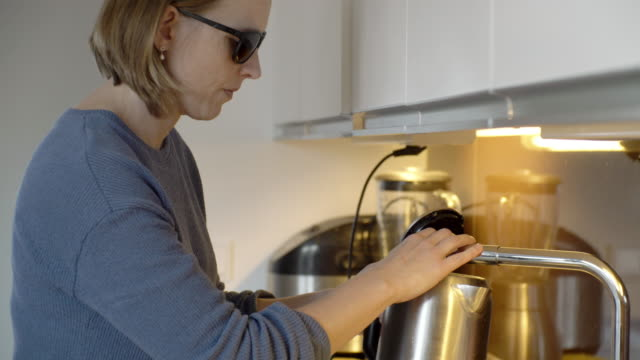 handheld shot of blind woman filling water in container from faucet at kitchen counter - visual impairment stock videos & royalty-free footage