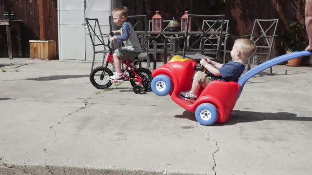 handheld shot of boy cycling by father pushing son sitting on toy car - pushing stock videos & royalty-free footage