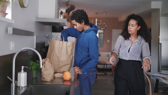 handheld shot of boy helping mother in kitchen while removing vegetables and fruits from groceries bag on counter - one parent stock videos & royalty-free footage