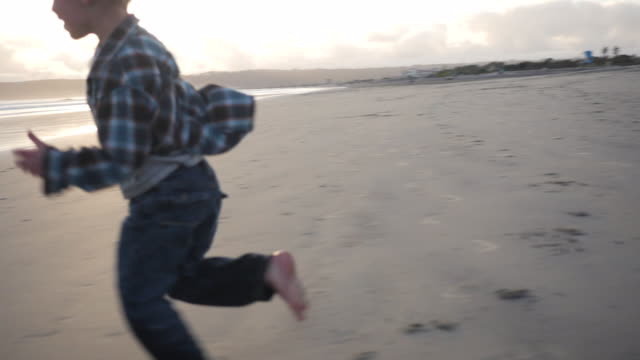 Handheld shot of boy running on shore at beach