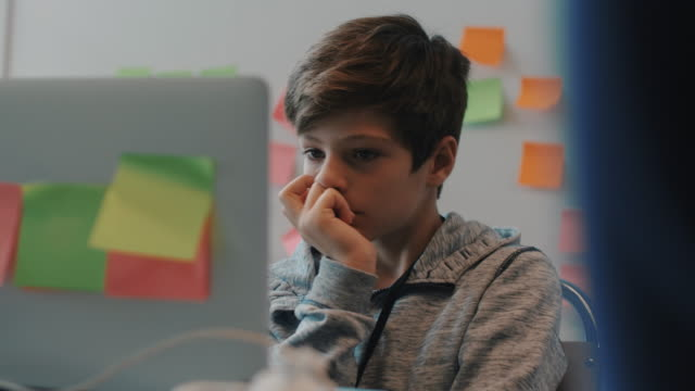 handheld shot of boy thinking while looking at laptop in training class - silenzio video stock e b–roll