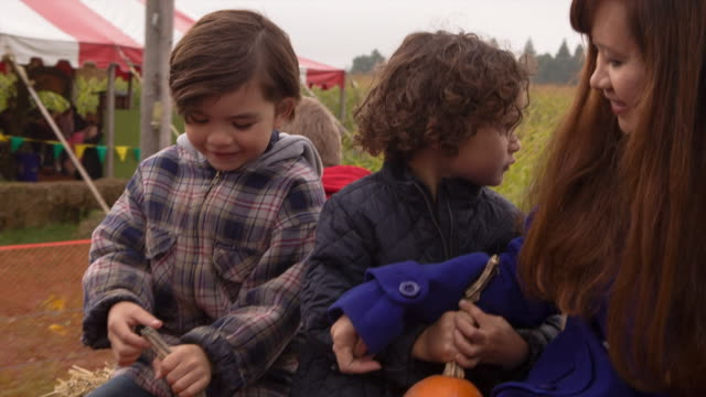 Handheld shot of boy traveling with mother on vehicle in pumpkin farm