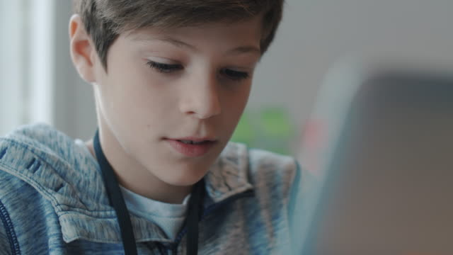 vídeos de stock e filmes b-roll de handheld shot of boy using laptop in training class - workshop