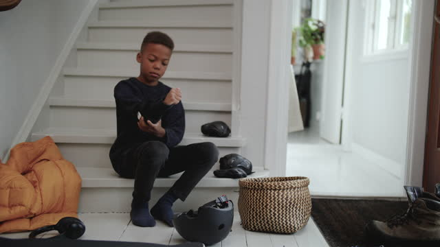 handheld shot of boy wearing elbow pad while sitting on steps at home entrance - sports helmet stock videos & royalty-free footage