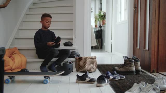 vídeos y material grabado en eventos de stock de handheld shot of boy wearing kneepad while sitting on steps at home entrance - equipo de seguridad